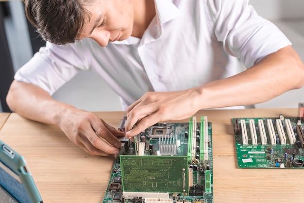 Nahaufnahme männlichen it-technikers, der das computer mainboard repariert Kostenlose Fotos