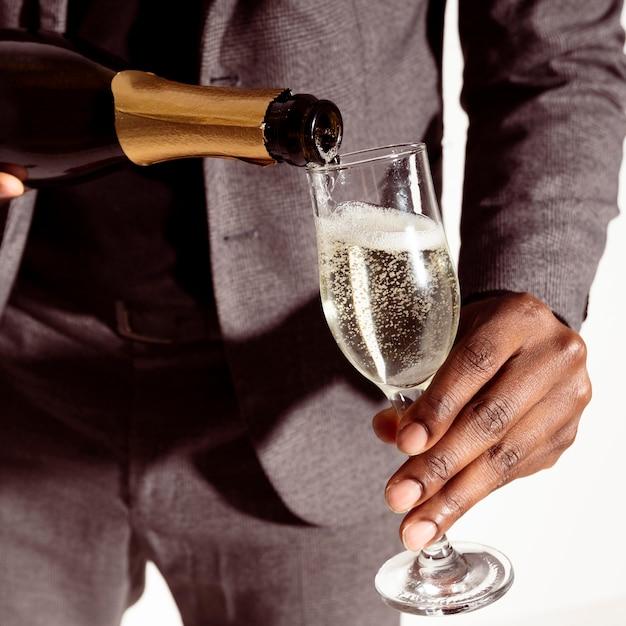 Nahaufnahme mann, der champagner in flasche gießt Kostenlose Fotos