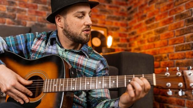 Nahaufnahme mann, der die gitarre spielt Kostenlose Fotos
