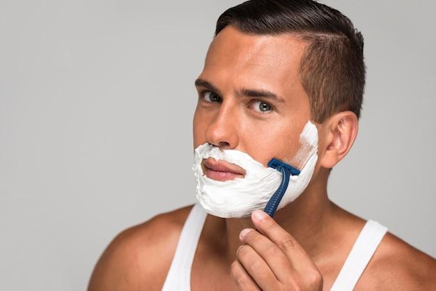 Nahaufnahme mann, der mit rasiermesser rasiert Premium Fotos