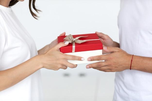 Nahaufnahme mann hände geben verpackte geschenkbox frau Premium Fotos