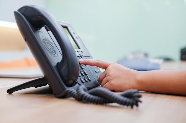 Nahaufnahme mann hand zeigt versuchen, taste nummer am telefon schreibtisch zu drücken Premium Fotos