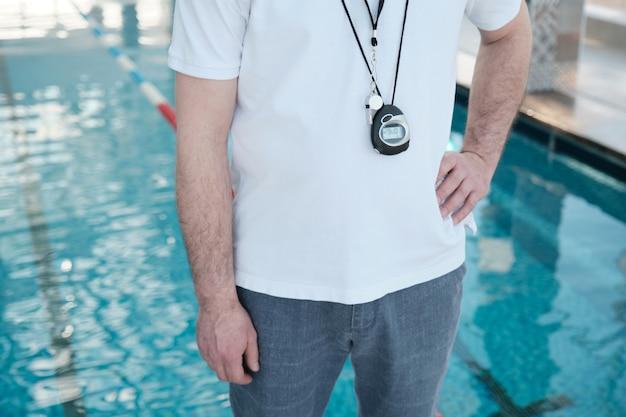 Nahaufnahme nicht erkennbarer schwimmtrainer mit stoppuhr und pfeife auf der brust stehend mit der hand auf der hüfte Premium Fotos