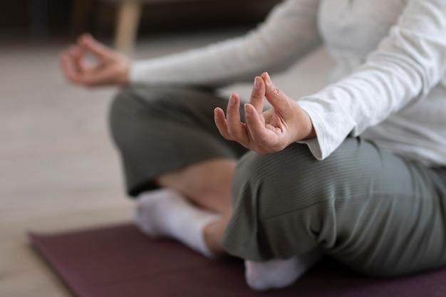 Nahaufnahme person, die zu hause meditiert Kostenlose Fotos