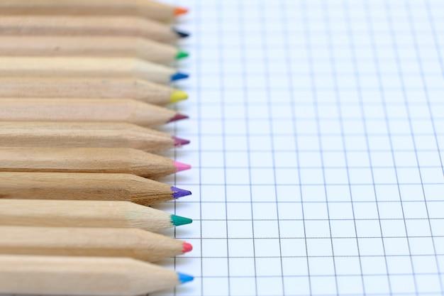 Nahaufnahme satz von bunten stiften auf dem karierten papierblatt des notizbuchs für die zeichnung. zurück zum schulkonzept. Premium Fotos
