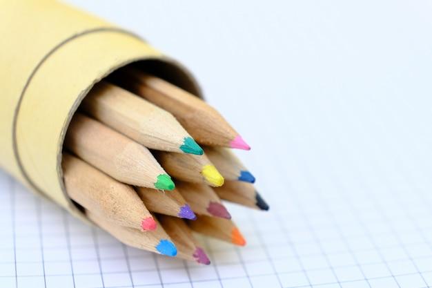 Nahaufnahme-satz von mehrfarbigen stiften in einer box auf kariertem papierblatt des notizbuchs für die zeichnung. zurück zum schulkonzept. Premium Fotos