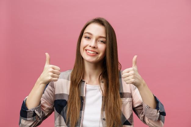 Nahaufnahme schoss vom lächelnden hübschen mädchen, das daumen herauf geste zeigt. Premium Fotos