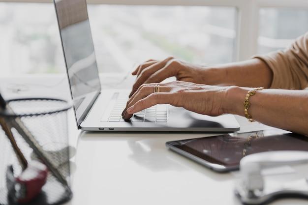 Nahaufnahme schoss von der person, die auf laptop schreibt Kostenlose Fotos