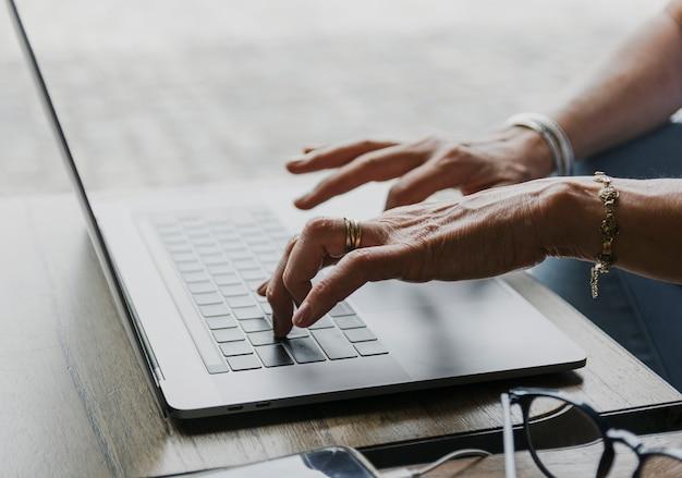 Nahaufnahme schoss von der person, die auf laptoptastatur schreibt Kostenlose Fotos