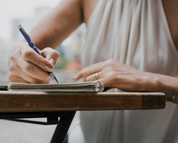 Nahaufnahme schoss von der person, die mit einem stift auf notizbuch schreibt Kostenlose Fotos