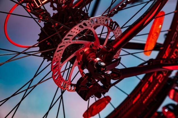 Nahaufnahme schoss von genannter mechanikerbremsscheibe auf fahrrad im roten künstlichen blitz Premium Fotos