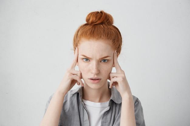 Nahaufnahme schuss der gestressten unglücklichen jungen kaukasischen frau, die ihr ingwerhaar im brötchen trägt, finger auf schläfen hält, unter starken kopfschmerzen, migräne leidet oder sich bemüht, sich an etwas zu erinnern Kostenlose Fotos