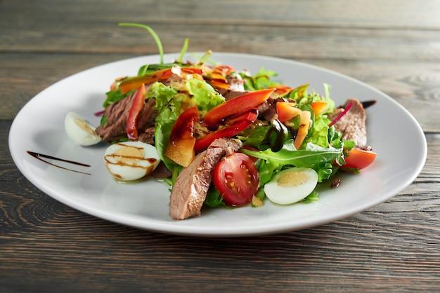 Nahaufnahme schuss des leckeren frischen salats mit gegrilltem fleisch und eiern und soßegrünpfeffer köstliches essen helthy ernährung mittagessen abendessen abendessen kulinarisches kochrezept zutaten. Kostenlose Fotos