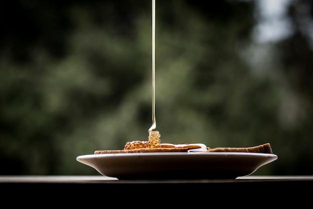 Nahaufnahme schuss von honig, der auf die brotscheiben auf einem teller gießt Kostenlose Fotos