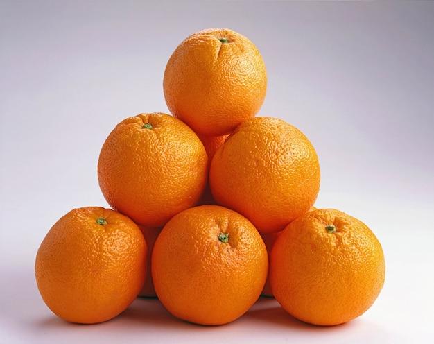 Nahaufnahme schuss von orangen übereinander auf einer weißen oberfläche - ideal für einen hintergrund Kostenlose Fotos