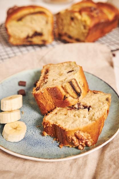 Nahaufnahme schuss von scheiben des köstlichen bananenbrotes mit schokoladenstücken und walnuss auf einem teller Kostenlose Fotos