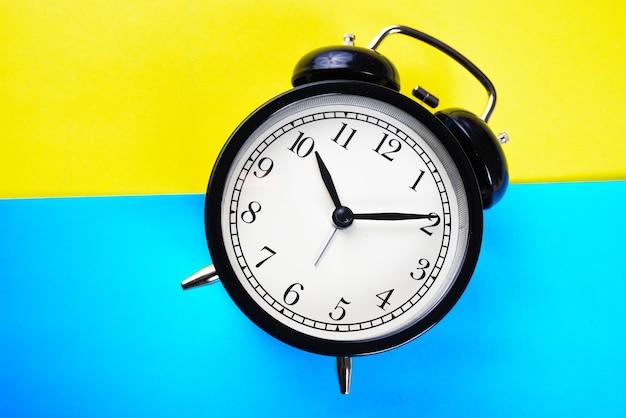 Nahaufnahme schwarzer wecker auf einem gelben und blauen Premium Fotos