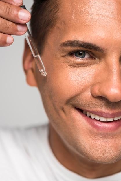 Nahaufnahme-smiley-mann, der serum anwendet Kostenlose Fotos