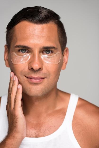 Nahaufnahme-smiley-mann mit unter augenklappen Premium Fotos