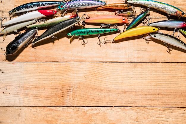 Nahaufnahme vieler bunter fischenköder auf hölzernem schreibtisch Kostenlose Fotos