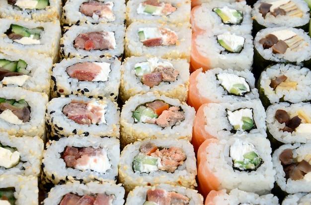 Nahaufnahme vieler sushirollen mit verschiedenen füllungen Premium Fotos