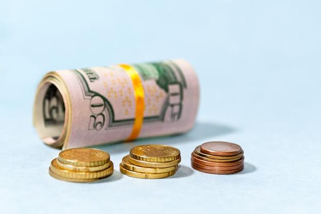 Nahaufnahme von aufgerollten us-dollar-banknoten und euro-münzen Premium Fotos