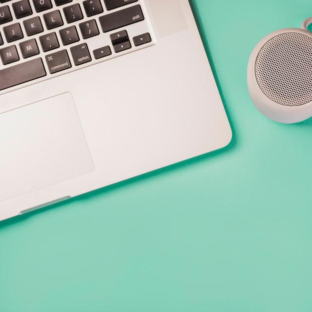 Nahaufnahme von bluetooth lautsprecher und laptop auf grünem hintergrund Kostenlose Fotos