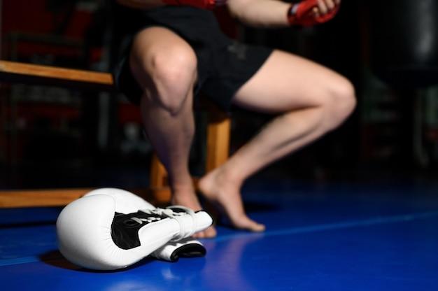 Nahaufnahme von boxerbeinen, die auf bank im fitnessstudio nach dem training ruhen. Premium Fotos