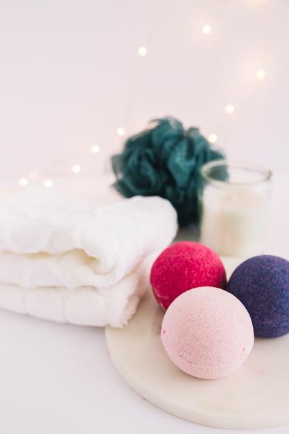 Nahaufnahme von bunten badebomben auf weißem brett nahe servietten und luffa Kostenlose Fotos