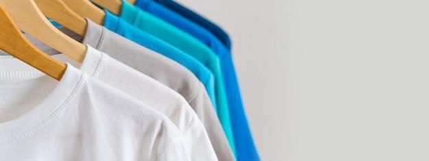 Nahaufnahme von bunten t-shirts auf kleiderbügeln Premium Fotos