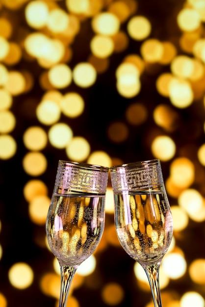 Nahaufnahme von champagnergläsern auf bokeh hellem hintergrund Kostenlose Fotos