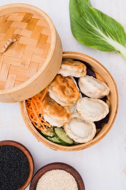 Nahaufnahme von chinesen gedämpften mehlklößen mit salat im dampfkorb mit schwarzweiss-samen des indischen sesams Kostenlose Fotos