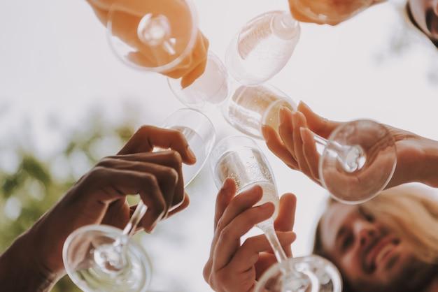 Nahaufnahme von clink champagne glasses in sun. Premium Fotos