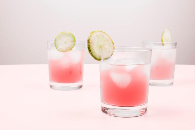 Nahaufnahme von cocktails auf dem rosa schreibtisch gegen grauen hintergrund Kostenlose Fotos