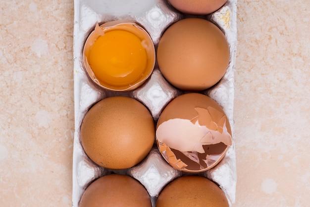 Nahaufnahme von defekten eiern im weißen karton auf beschaffenheitshintergrund Kostenlose Fotos