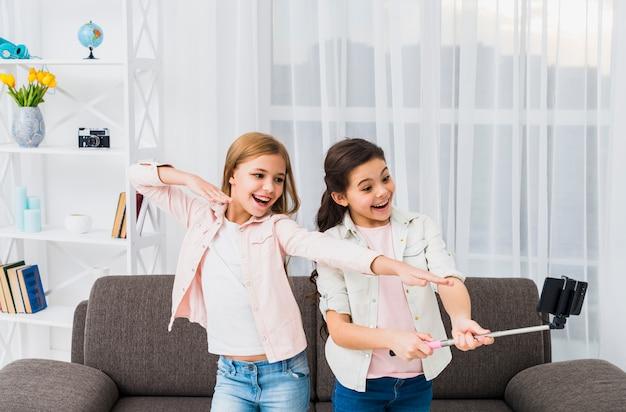 Nahaufnahme von den freundinnen, die selbstporträt am intelligenten telefon im wohnzimmer nehmen Kostenlose Fotos