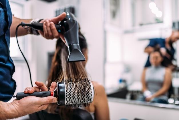 Nahaufnahme von den friseurhänden, die langes haar mit föhn und rundbürste trocknen. Premium Fotos