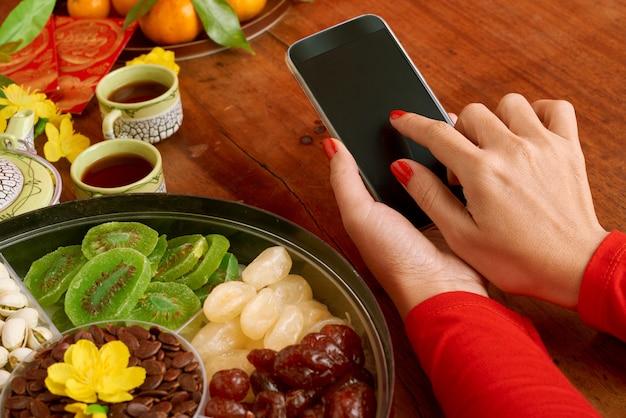 Nahaufnahme von den geernteten weiblichen händen, die smartphone auf einem gedienten abendtische halten Kostenlose Fotos
