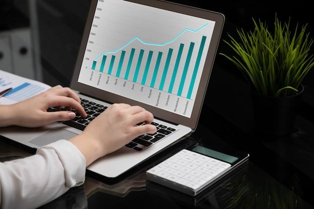 Nahaufnahme von den händen, die auf laptop mit leerem schwarzem bildschirm nahe bei diagrammen und taschenrechner schreiben Premium Fotos