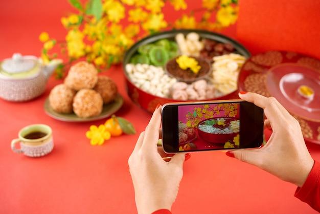 Nahaufnahme von den händen, die fotos von tet feiertagslebensmittel auf smartphonekamera machen Kostenlose Fotos
