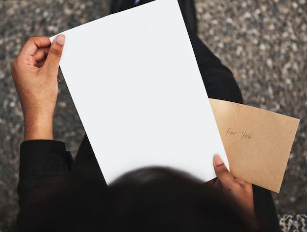 Nahaufnahme von den händen, die leeres papier halten Premium Fotos