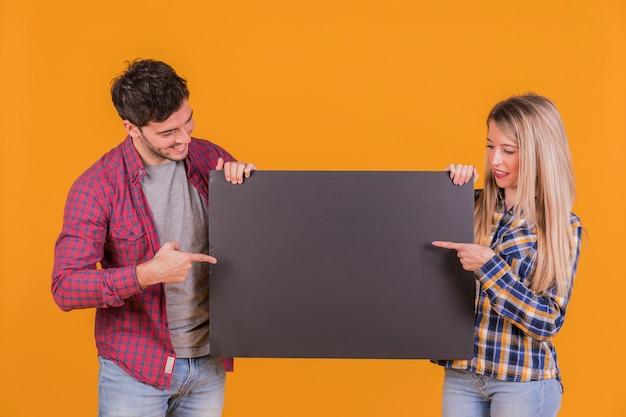 Nahaufnahme von den jungen paaren, die ihre finger auf dem schwarzen plakat gegen einen orange hintergrund zeigen Kostenlose Fotos