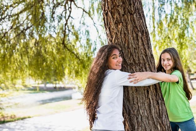 Nahaufnahme von den lächelnden mädchen, welche die hand umarmt großen baum im park halten Kostenlose Fotos
