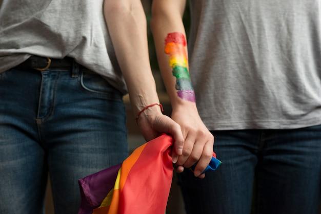 Nahaufnahme von den lesbischen paaren, die lbgt flagge in den händen halten Premium Fotos