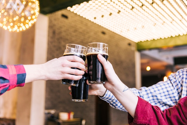 Nahaufnahme von den männern, welche die biergläser in der kneipe klirren Kostenlose Fotos