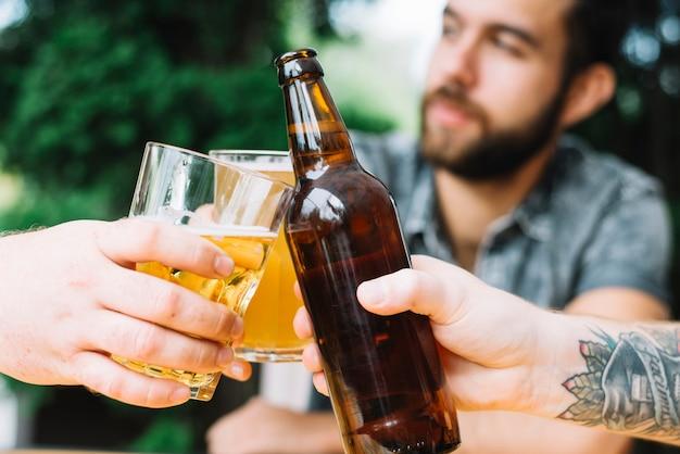 Nahaufnahme von den männlichen freunden, die zu hause mit alkoholischen getränken zujubeln Kostenlose Fotos