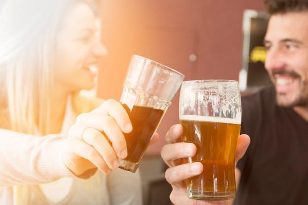 Nahaufnahme von den paaren, die glas bier rösten Kostenlose Fotos