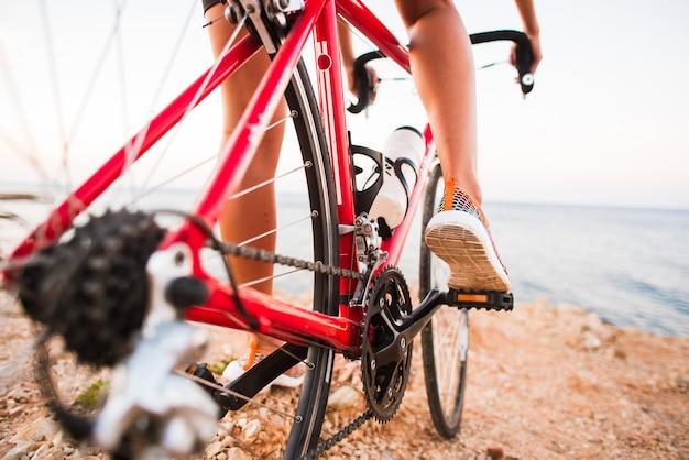 Nahaufnahme von den radfahrerfrauenbeinen, die fahrrad auf spur im freien reiten Premium Fotos