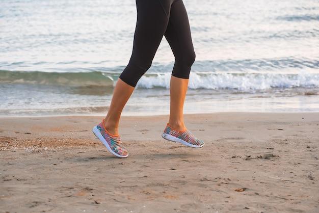Nahaufnahme von den weiblichen beinen, die auf strand bei sonnenaufgang am morgen laufen Premium Fotos