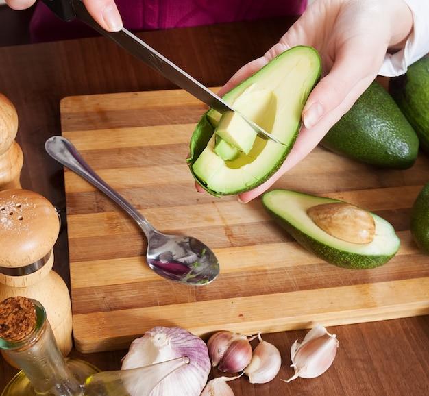 Nahaufnahme von den weiblichen händen kochend mit avocado Kostenlose Fotos